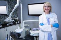 Retrato de dentista sorridente de pé com os braços cruzados na clínica odontológica — Fotografia de Stock