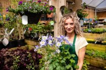 Retrato de florista feminino segurando em vaso de planta no jardim centro — Fotografia de Stock