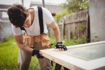 Tischler arbeitet am Türrahmen auf dem Rasen — Stockfoto