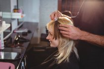 Male hairdresser styling customers hair at salon — Stock Photo