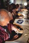 Сосредоточенный старший ювелир мужского пола, формирующий дерево в мастерской — стоковое фото