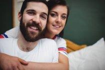 Mulher abraçando o homem na cama no quarto — Fotografia de Stock