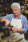Sênior sapateiro masculino reparando um sapato na oficina — Fotografia de Stock