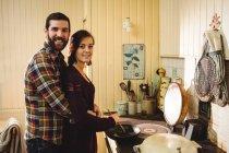 Объятие пара готовит еду вместе на кухне дома — стоковое фото