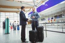 Les gens d'affaires en attente au check-in compteur avec bagages dans l'aérogare — Photo de stock
