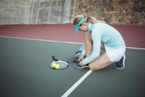 Female tennis player tying shoe lace in sport court — Stock Photo