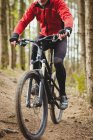 Вид спереди на горного байкера, едущего по проселочной дороге в лесу — стоковое фото