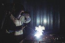 Жіночий зварювальник, працюючи на шматок металу в майстерні — стокове фото