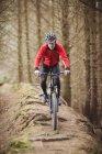 Вид спереди мужчины-байкера, едущего по колейной дороге у деревьев в лесу — стоковое фото