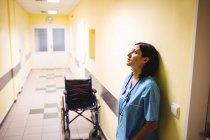 Depressed nurse standing in hospital corridor — Stock Photo