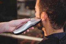 Immagine ritagliata di uomo ottenere la sua barba tagliata al salone di parrucchiere — Foto stock
