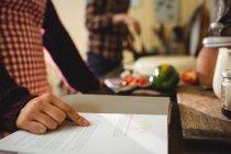 Sección media de mujer leyendo un libro de recetas de cocina en casa - foto de stock
