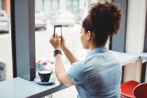 Woman using phone while siting at restaurant — Stock Photo