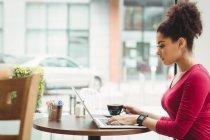 Femme utilisant un ordinateur portable tout en étant assis au restaurant — Photo de stock