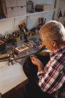 Attentive goldsmith using hand piece machine in workshop — Stock Photo