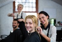 Portrait of smiling hairstylist combing client hair in salon — Stock Photo