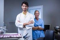Retrato del dentista sonriente y asistente dental de pie con los brazos cruzados en la clínica dental - foto de stock
