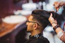 Uomo ottenere i capelli tagliati con forbice in negozio di barbiere — Foto stock