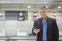 Uomo d'affari che utilizza il telefono cellulare in sala d'attesa presso il terminal dell'aeroporto — Foto stock