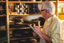 Senior-Schuhmacher schreibt in Werkstatt auf Klemmbrett — Stockfoto