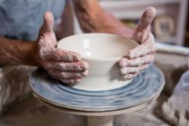 Mid section of potter making pot in pottery shop — Stock Photo