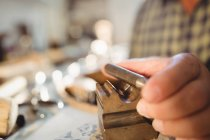 Cropped image of goldsmith preparing ring in workshop — Stock Photo