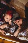 Висока кут зору молода пара, за допомогою мобільного телефону на ліжку у себе вдома — стокове фото
