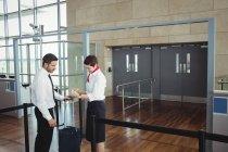 Homme d'affaires montrant sa carte d'embarquement au comptoir d'enregistrement à l'aéroport — Photo de stock