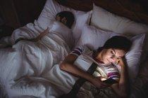 Mujer usando el teléfono móvil mientras está acostado en la cama en el dormitorio - foto de stock