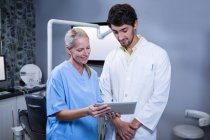 Dentist and dental assistant working together with tablet at dental clinic — Stock Photo