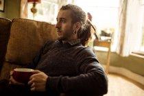 Вид сбоку на хипстера, который держит чашку кофе, расслабляясь на диване дома — стоковое фото