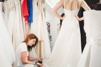 Woman trying on wedding dress in studio with assistance of creative designer — Stock Photo