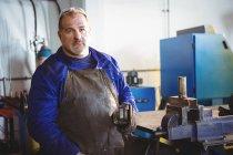 Retrato de soldador segurando serra elétrica na oficina — Fotografia de Stock
