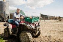 Retrato de agricultor equitação quadbike no campo — Fotografia de Stock