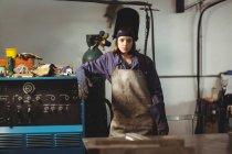 Портрет женщины-сварщика, стоящей рядом с машиной в мастерской — стоковое фото