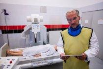 Arzt mit digitalem Tablet und Patient liegen im Krankenhaus auf Röntgengerät — Stockfoto