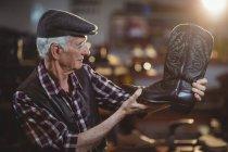 Sapateiro sênior em cap examinando um sapato na oficina — Fotografia de Stock