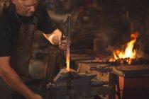 Herrero trabajando en una varilla de hierro calentada en el taller - foto de stock