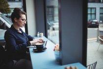 Молода ділова жінка працює на ноутбуці в кафе. — стокове фото