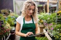 Florista feminina usando tablet digital no centro de jardim — Fotografia de Stock