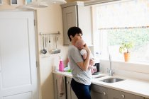 Mother holding her little baby in kitchen at home — Stock Photo