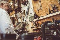 Горолог смотрит на машину в мастерской — стоковое фото