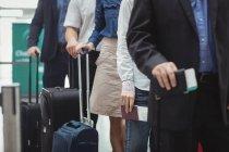 Passagiere mit Pässen und Bordkarte warten in der Warteschlange im Flughafenterminal — Stockfoto