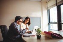 Hombre y mujer discutiendo sobre tableta digital y portátil en la oficina - foto de stock