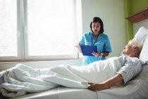 Медсестра, взаимодействующая с пациентом в больнице — стоковое фото
