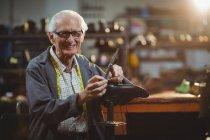 Smiling shoemaker hammering on a shoe in workshop — Stock Photo