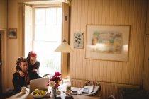 Casal jovem usando laptop em casa — Fotografia de Stock