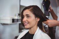 Офіціантка, отримуючи її волосся сушать фен для волосся в перукарні — стокове фото