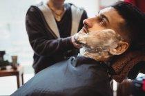Un hombre afeitándose la barba en la peluquería - foto de stock