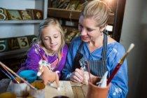 Жіночий Поттер допомога дівчина в живопису гончарної майстерні — стокове фото